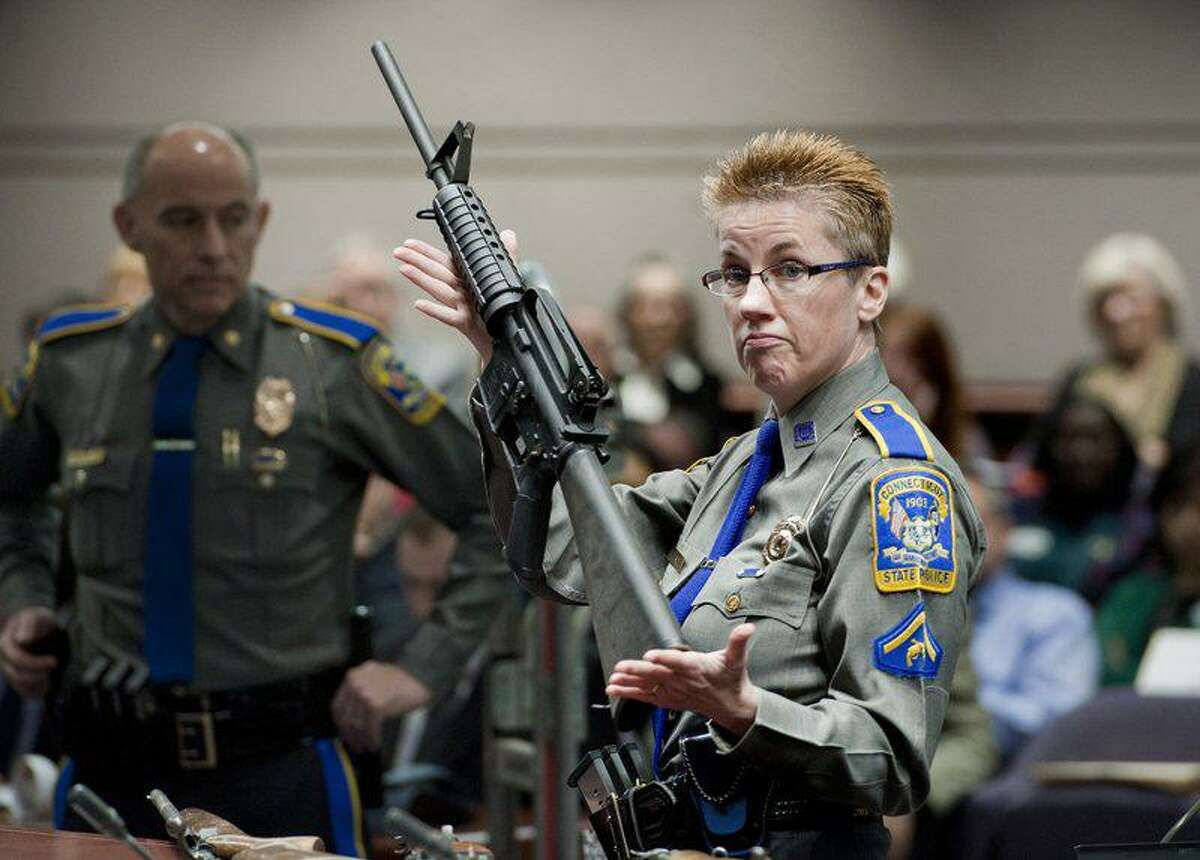 FILE - In this 2013, file photo, firearms training unit Detective Barbara J. Mattson, of the Connecticut State Police, holds up a Bushmaster AR-15 rifle made by Remington Arms, the same make and model of the gun used by Adam Lanza in the December 2012 Sandy Hook School shooting.