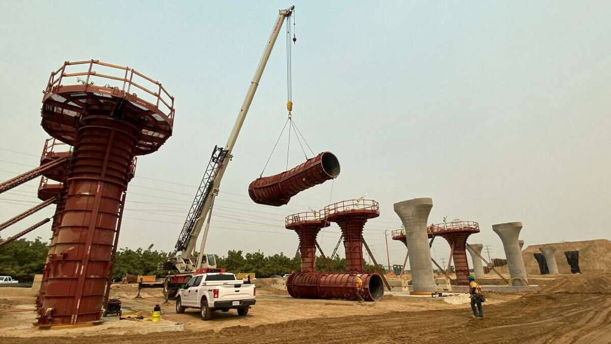 Crews hoist the forms for the columns into place before concrete is poured to form a column on the Hanford Viaduct in Kings County, part of the construction for the California high-speed rail project, in August 2020.