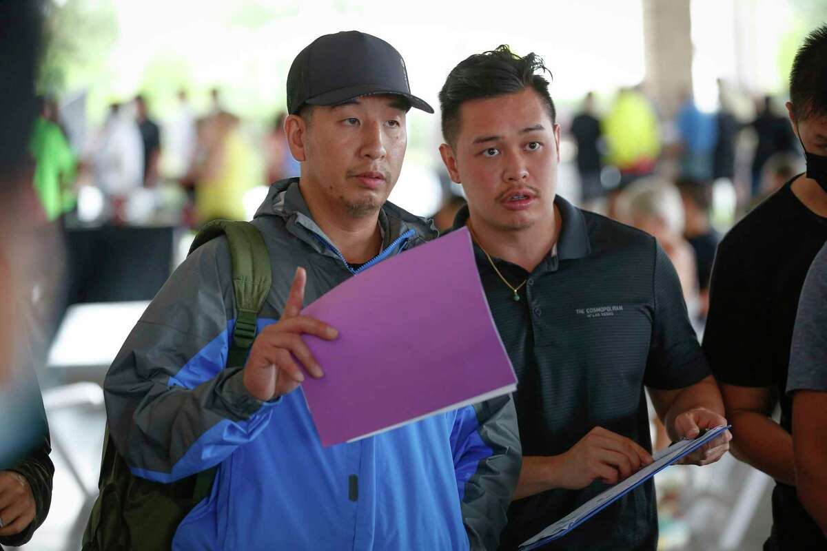 Sam Nguyen (right) and his buying partner, David, place a winning bid on a property during July's foreclosure auction at the Bayou City Event Center Tuesday, July 6, 2021, in Houston.
