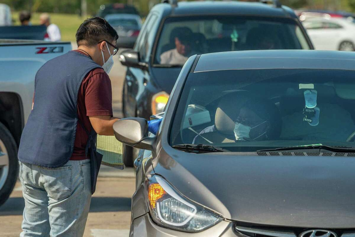 Poll worker John Nguyen takes a portable voting machine from a disabled voter after the woman casther ballot outside the Port Arthur Public Library on Election Day in 2020.