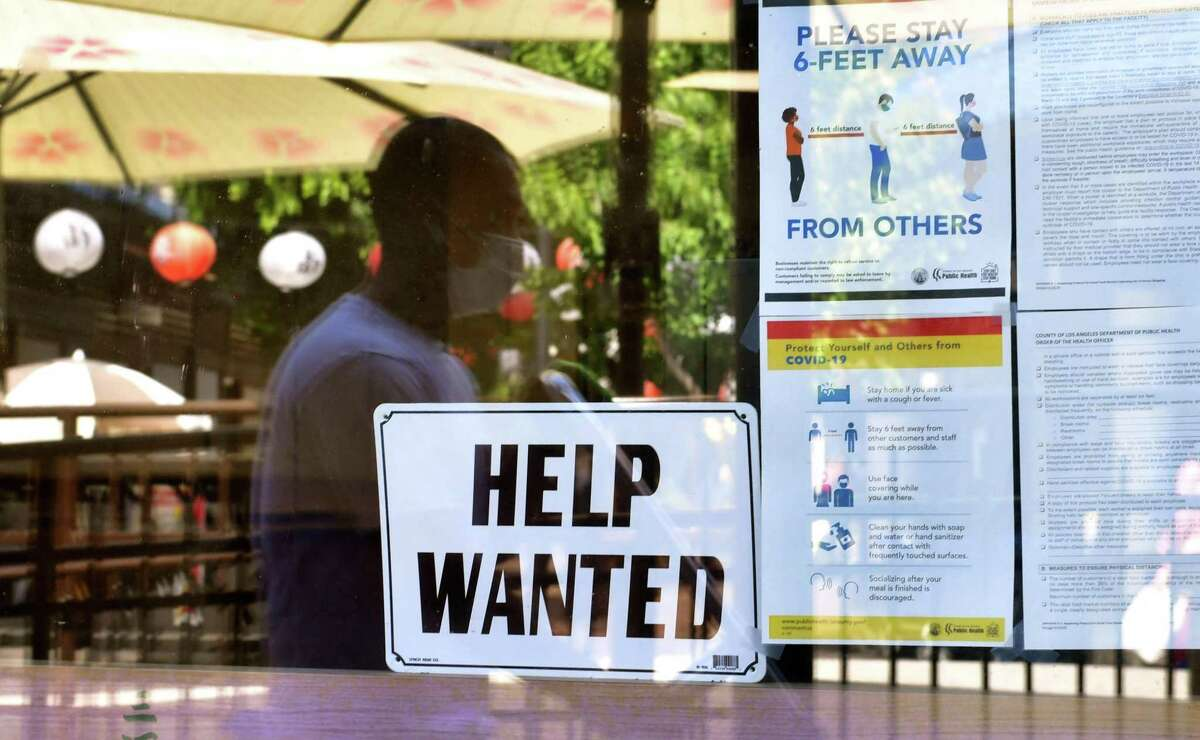 """A """"Help Wanted"""" sign is posted beside Coronavirus safety guidelines in front of a restaurant in Los Angeles. A report from UC Berkeley Labor Center found that low-wage workers and workers of color are stiill struggling to find jobs, or are worried about returning to high risk jobs."""
