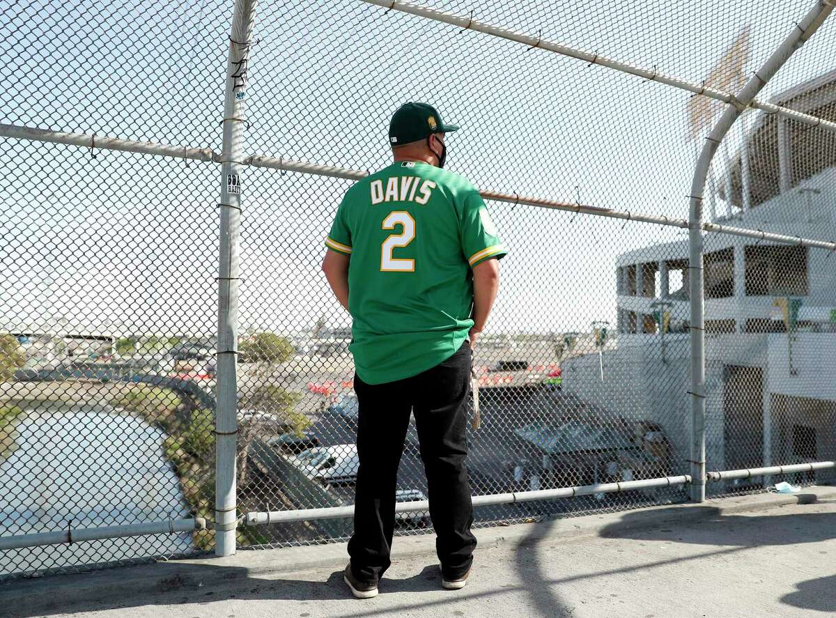 Silvano Campos Perez of St. Helena waits on the BART overpass to be let into the stadium before the Oakland Athletics season opener at the Oakland Coliseum in April. The city is planning to sell its stake in the Coliseum.