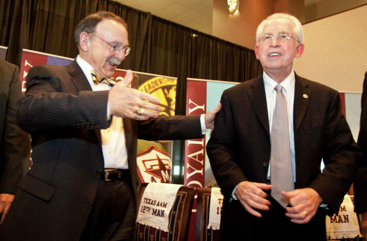 Former Texas A&M president R. Bowen Loftin, left, shaking hands with former Southeastern Conference commissioner Mike Slive on the school's induction into the conference in 2011, recalls how Texas and the Longhorn Network gave a boost to the school's move.