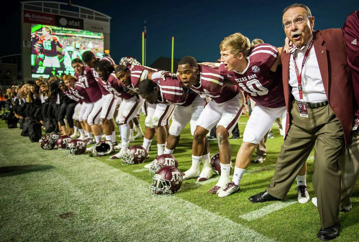 Texas A&M president R. Bowen Loftin lines up with the football team for the singing of the Aggie War Hymn after their victory over Sam Houston State on Saturday, Nov. 17, 2012, in College Station.