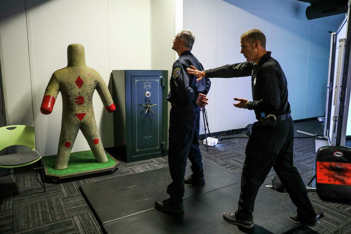 Sgt. Steven Pomatto and Sgt. John Crudo (left) of the San Francisco Police Department demonstrate how they teach use-of-force using hands-on techniques as well as the VirTra simulator to introduce scenarios.