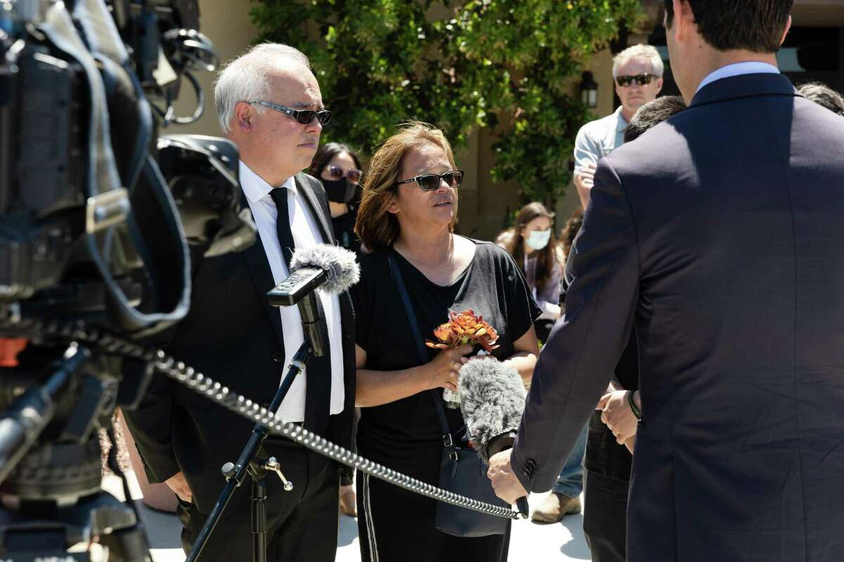 Robert Collins (left) and Cassandra Quinto-Collins give an interview after her son Angelo Quinto's committal service at Holy Cross Cemetery and Funeral Center.