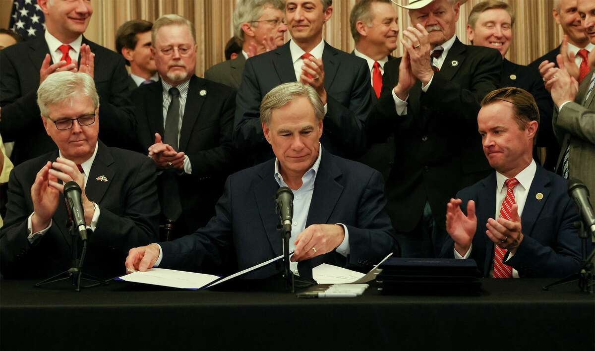 """Texas Governor Greg Abbott, center, seated next to Lieutenant Governor Dan Patrick, left, and Speaker Dade Phelan prepares to sign a """"constitutional carry"""" bill allowing Texans to carry handguns without a permit along with several other pieces of legislation relating to the Second Amendment in Alamo Hall at the Alamo on Thursday, June 17, 2021. The bills are scheduled to take effect on September 1."""