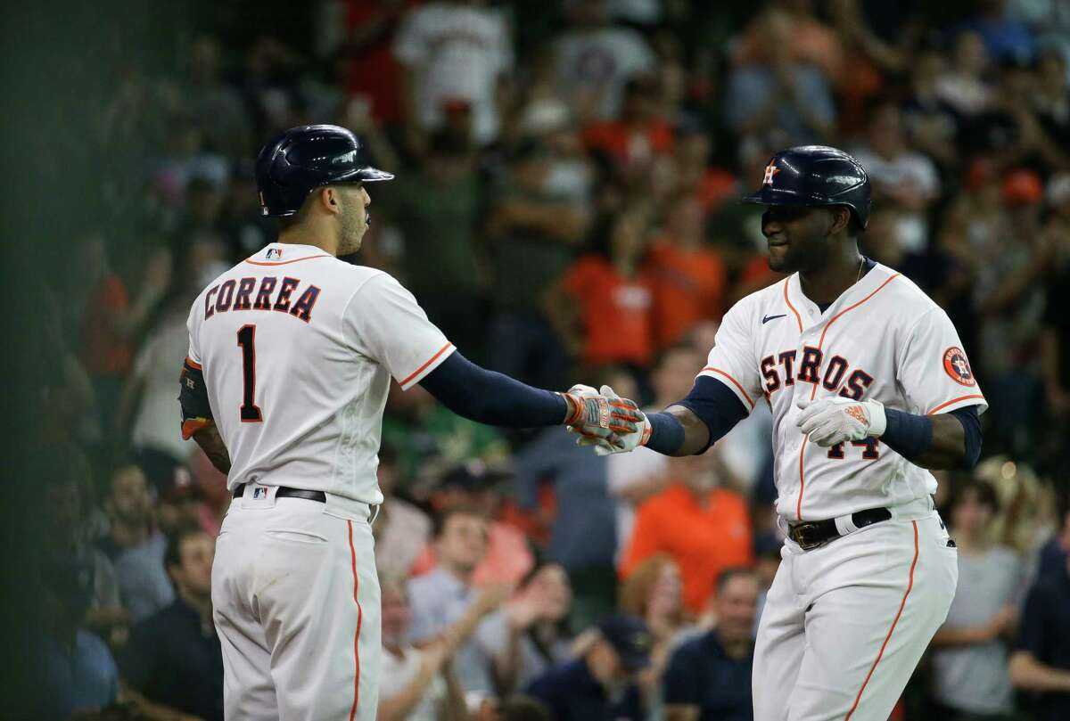 In his first game back from paternity leave, Yordan Alvarez (left) gave Carlos Correa and his Astros teammates a lift with two home runs and five RBIs to spark Tuesday's comeback win over the A's at Minute Maid Park.