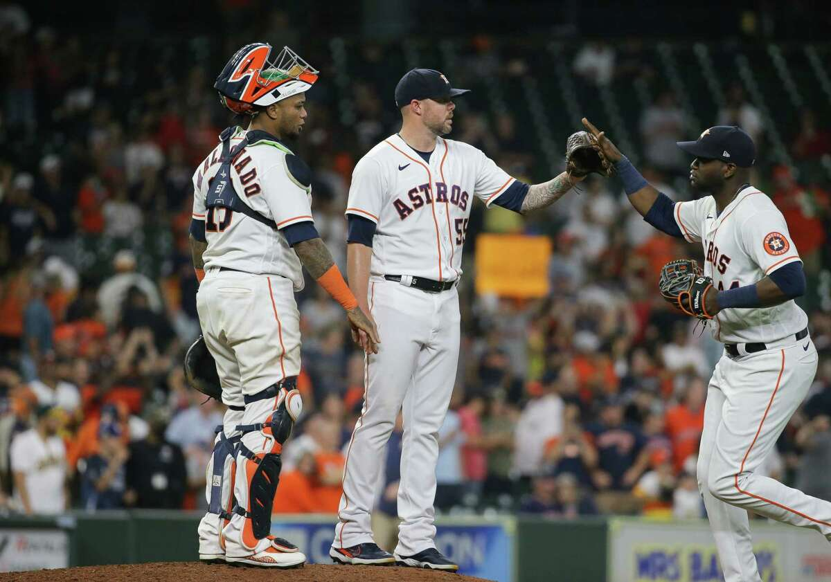 Houston Astros relief pitcher Ryan Pressly (55) celebrates with teammates after defeating the Oakland Athletics 9-6 at Minute Maid Park on Tuesday, July 6, 2021, in Houston.