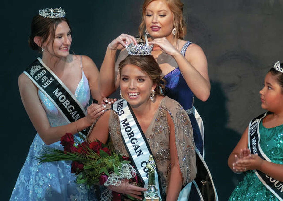 Julianne Wilson (center) gets crowned as the 2021 Morgan County Queen during the opening day of the county's fair while 2019 Junior Miss Kayla Brackett (left), 2019 Queen Lori Jackson (standing) and 2019 Little Miss Aleah Walls crown Wilson. To view more photos, visit: myjournalcourier.com