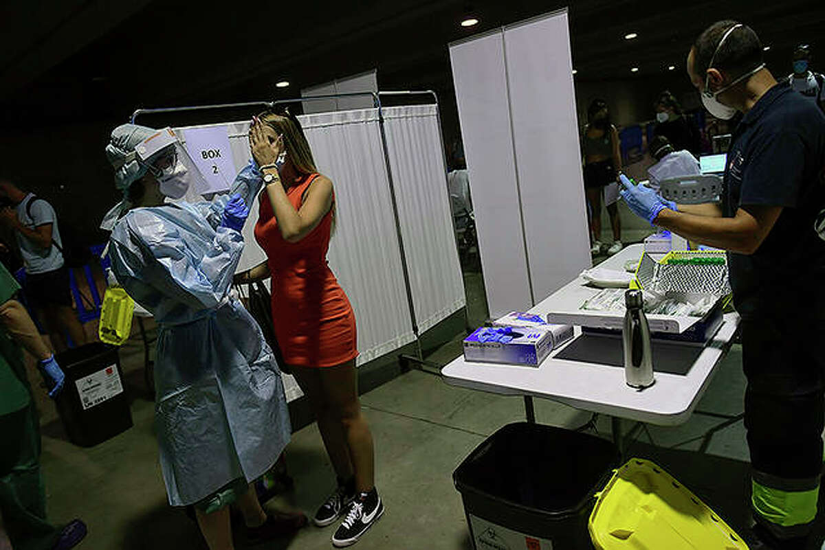 A health worker takes a swab from a teenager during a test for COVID-19.