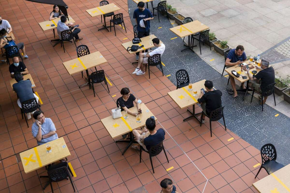 Customers sit at socially distanced tables outside a restaurant in Singapore, on Monday, June 21, 2021. Singapore has decided to scale down its reopening plans amid dozens of new cases over the last week, even as some countries with similarly high rates of vaccination allow a resumption of social activities and freer travel.