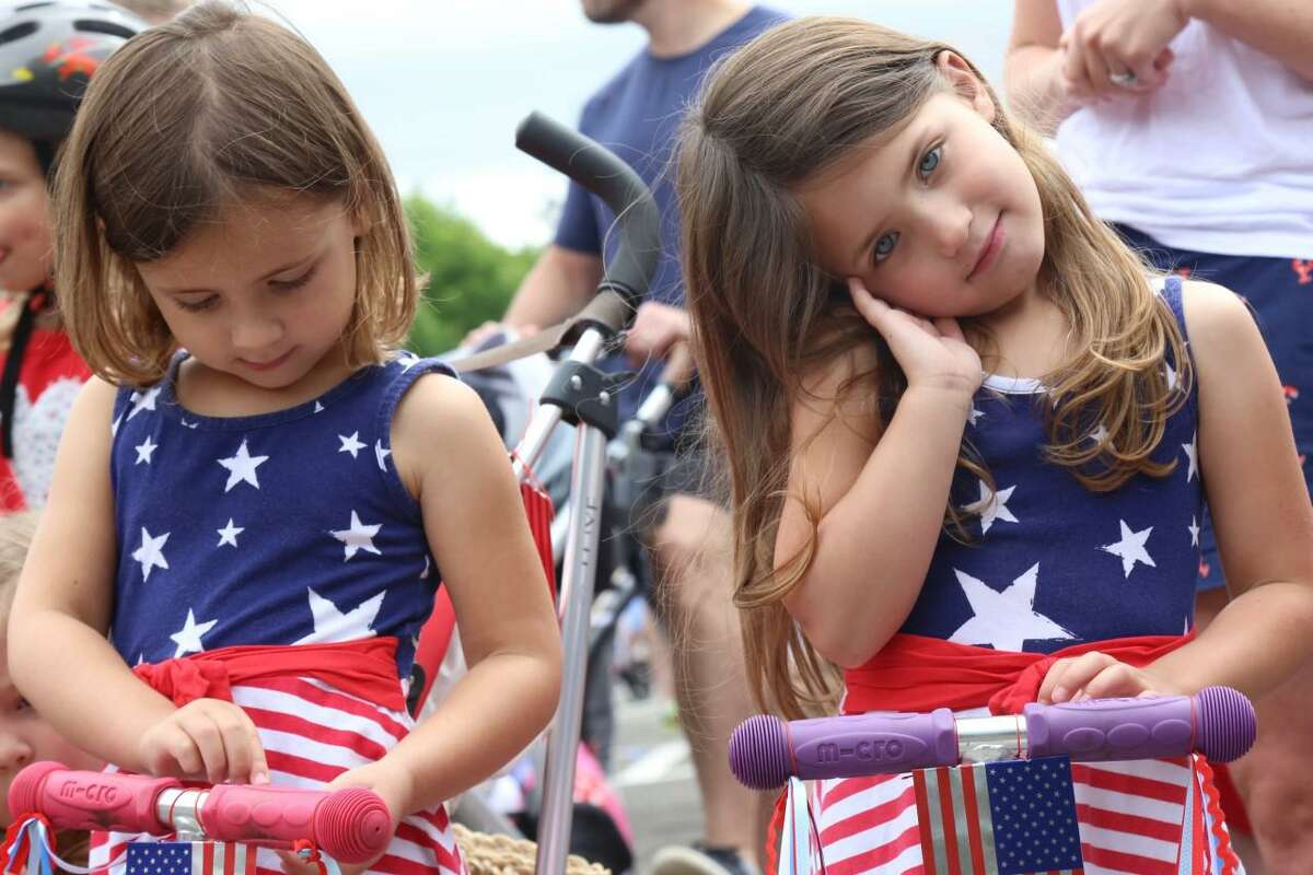 Twins sisters Nora, left, and Maeve Casey, age 4, were in the holiday spirit at the Pull-N-Pull Parade at Darien High School on Sunday, July 4, 2021.