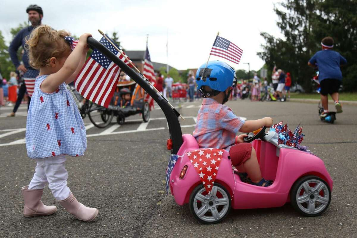 Parker Farris, 2, left, practices parading with Peyton Mathis, 2, at the Pull-N-Pull Parade at Darien High School on Sunday, July 4, 2021.