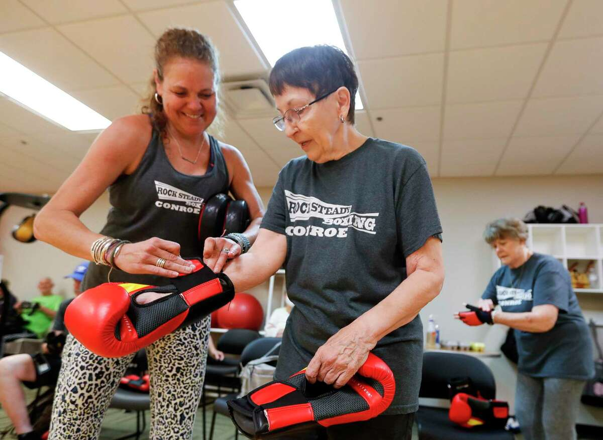 Ellen Wallace, center, gets help from instrutor Lisa Stultz putting on her boxing gloves during Rock Steady Boxing at the C.K. Ray Recreation Center, Friday, July 2, 2021, in Conroe. The weekly workout uses the basic functions of boxing to help residents with Parkinson disease strengthen areas of the brain affected by the disease such as balance, motor skills, and basic functions.