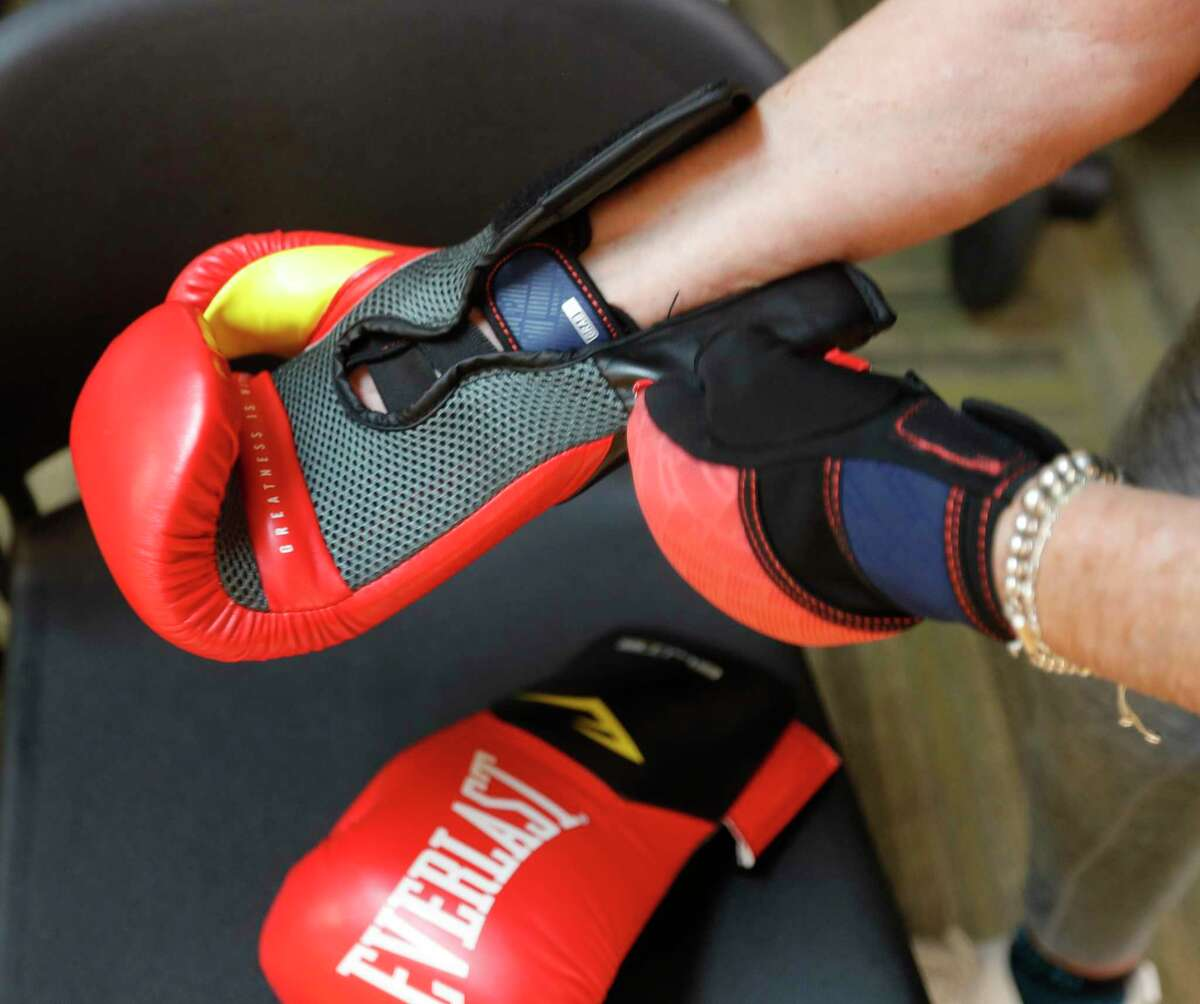 Ellen Wallace tries strapping on her boxing gloves during Rock Steady Boxing at the C.K. Ray Recreation Center, Friday, July 2, 2021, in Conroe. The weekly workout uses the basic functions of boxing to help residents with Parkinson disease strengthen areas of the brain affected by the disease such as balance, motor skills, and basic functions.