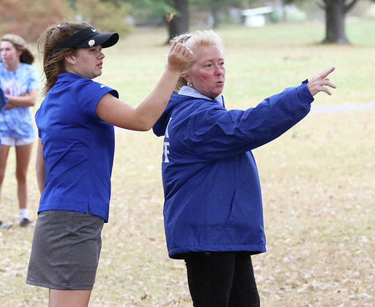 Marquette Catholic coach Deb Walsh (right) talks over a shot with Clancy Maag at the Class 1A sectional last season in Salem. Walsh is the 2020 Telegraph Girls Golf Coach of the Year.