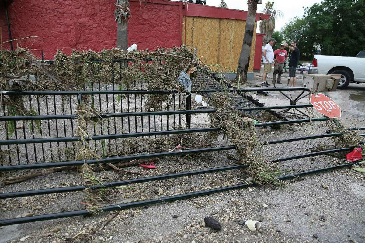 Logan Rhodes (from right), Sal Ramos and Nate Brown stand near damaged gates and debris at the Comfort Cafe located at 5618 Bandera Road after a catastrophic flood from the heavy rainstorms pounded parts of the city on Tuesday, July 6, 2021. The cafe owners support the addiction recovery program, Serenity Star, where some of the program's peers help run the restaurant. Their restaurant is a nonprofit - everyone who works here is in recovery and volunteer their services. They ask customers who come here to eat to pay a suggested $10 donation or whatever they can afford. The restaurant is totaled - they estimate the flood waters reached 4 and a half feet high. Wet mud is covering everything.