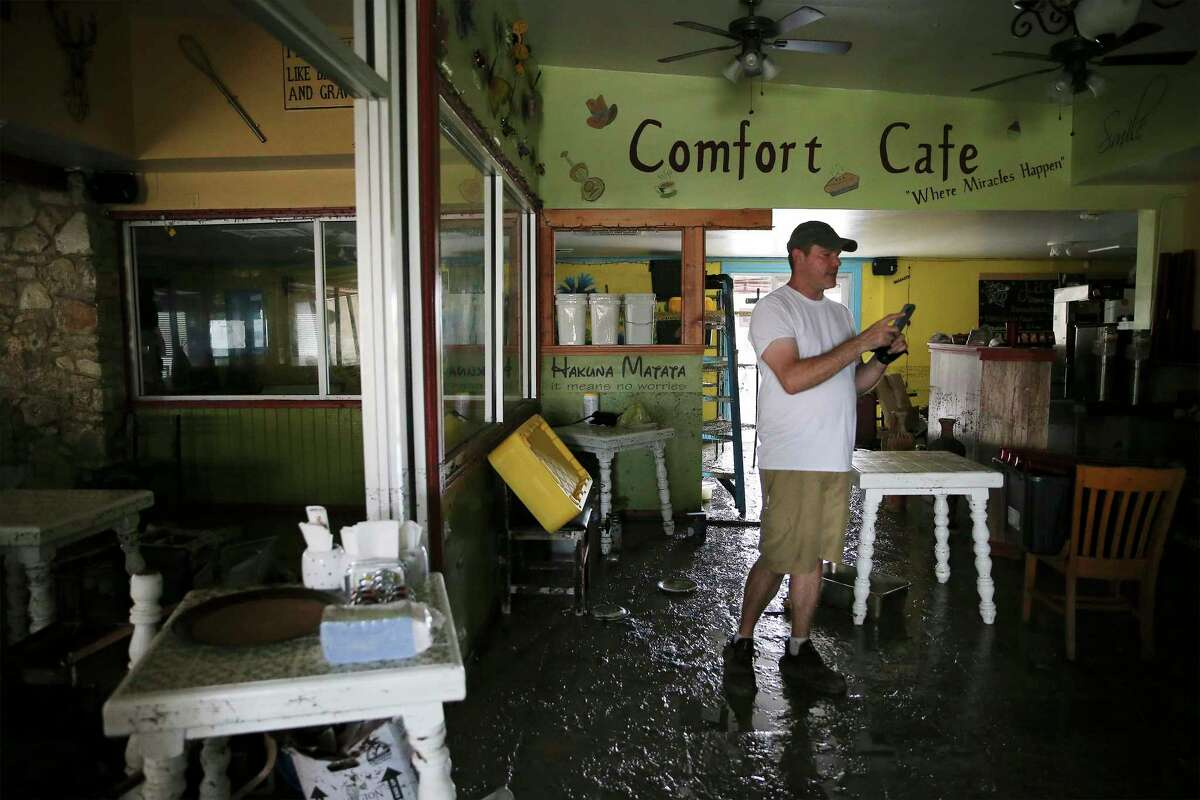 Nate Brown walks amongst a mud-strewn dining area of the Comfort Cafe located at 5618 Bandera Road after a catastrophic flood engulfed the building as a result of the heavy rainstorms that pounded parts of the city on Tuesday, July 6, 2021. The cafe owners support the addiction recovery program, Serenity Star, where some of the program's peers help run the restaurant. Brown is in the program. Their restaurant is a nonprofit - everyone who works here is in recovery and volunteer their services. They ask customers who come here to eat to pay a suggested $10 donation or whatever they can afford. The restaurant is totaled - they estimate the flood waters reached 4 and a half feet high. Wet mud is covering everything.