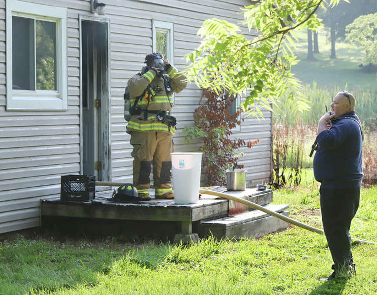 Rosewood Heights Fire Chief Tim Bunt, right, talks to his responding firefighters Wednesday morning as a Cottage Hills firefighter prepares to enter an unoccupied house in the 600 block of Wood River Avenue in Cottage Hills. No injuries were reported.