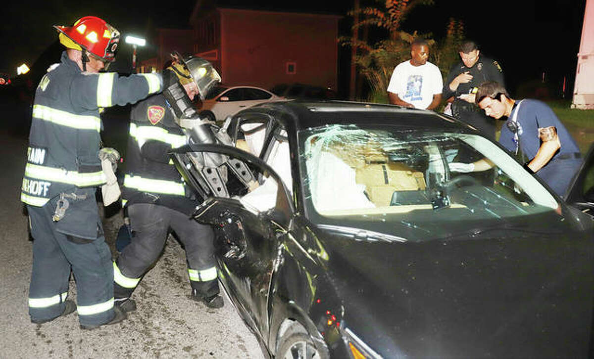Alton firefighters use a hydraulic rescue tool late Tuesday evening to free the passenger of a Nissan Sentra after the car was struck broadside by a hit and run driver who fled the scene on Highland Avenue about 10:05 p.m. Two people were hurt in the incident.