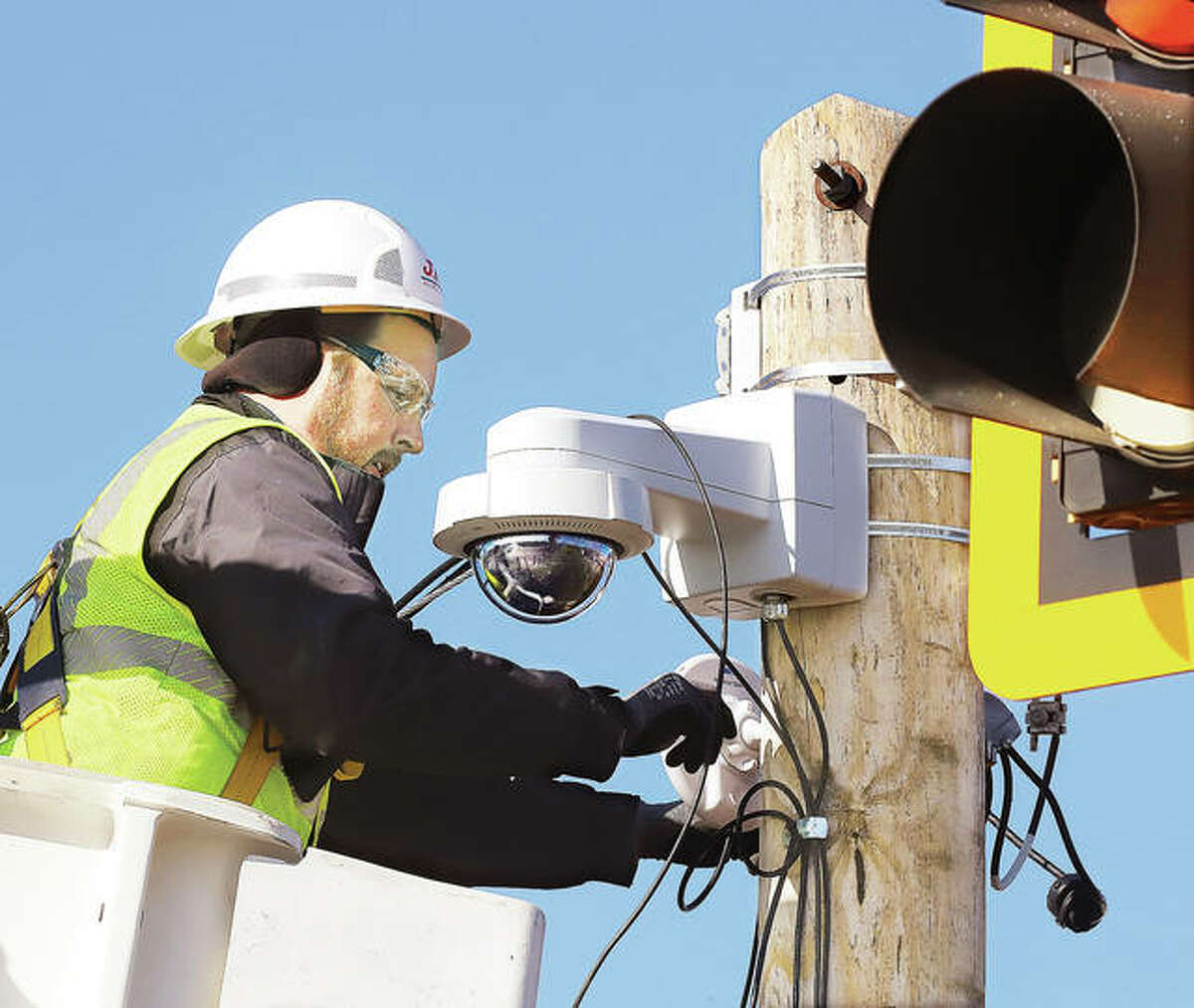 A J.F. Telecom employee wires up a camera on Landmarks Boulevard in December 2019 at the end of the Clark Bridge in Alton. More than 40 new license plate reader cameras are being considered in Madison County.
