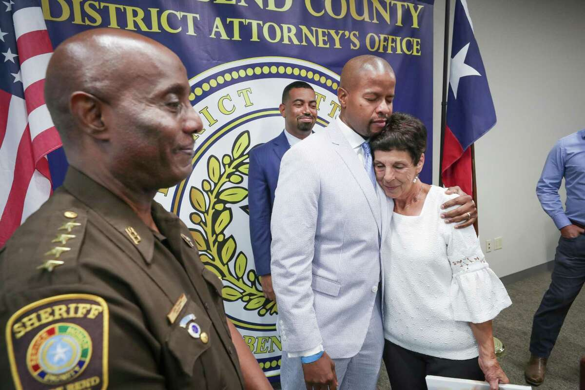 State Representative Ron Reynolds hugs Elaine Brooks, mother of Lisa Torry Smith as Fort Bend Sheriff Eric Fagan (left) and District Attorney Brian Middleton stand after a press conference to announce the passage of a bill creating criminal penalties for striking and killing a pedestrian in a crosswalk Tuesday, July 6, 2021, in Richmond.