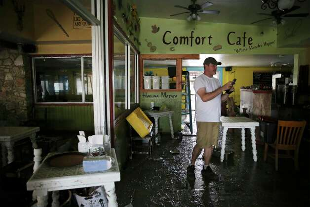 Nate Brown walks through a mud-strewn dining area of the Comfort Cafe on Bandera Road. Photo: Kin Man Hui /Staff Photographer / **MANDATORY CREDIT FOR PHOTOGRAPHER AND SAN ANTONIO EXPRESS-NEWS/NO SALES/MAGS OUT/ TV OUT
