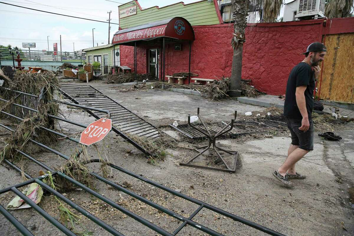 Logan Rhodes walks in a field of damaged gates and debris in front of the Comfort Cafe located on Bandera Road after a catastrophic flood from the heavy rainstorms that pounded parts of the city on Tuesday.