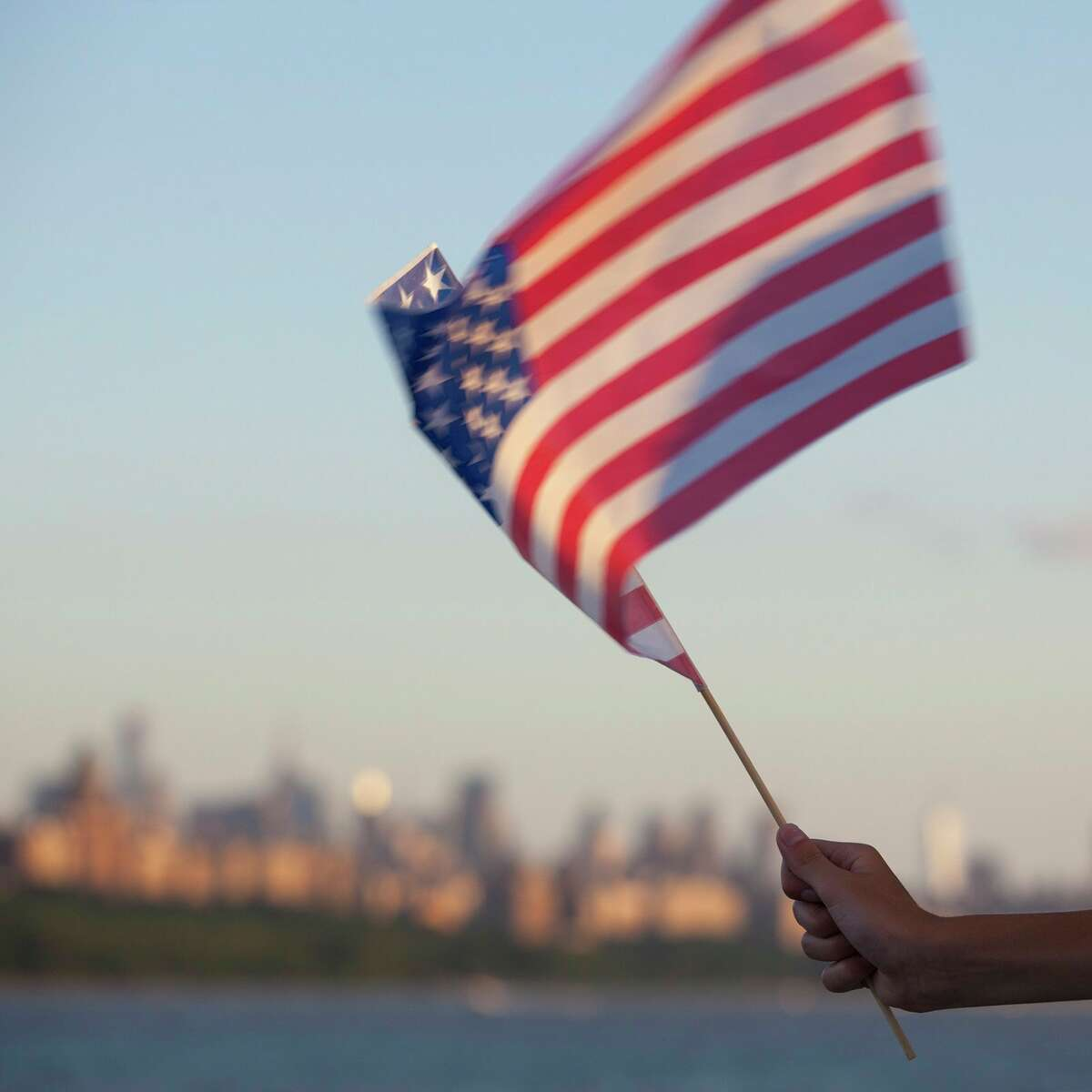 An American flag is waved near the Hudson River in New York City on July 4, 2013. (Dreamstime/TNS)