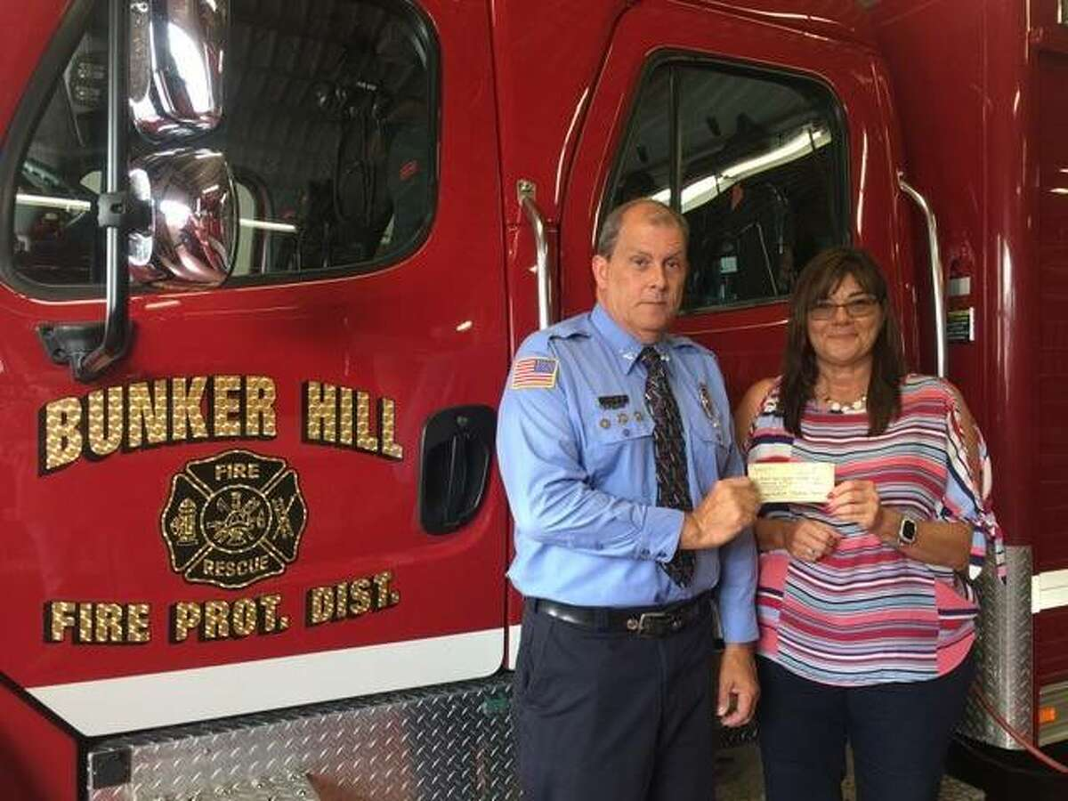 Boe Yeager of the Bunker Hill Fire Department receives a check from Michelle Mueller from proceeds of a May 15 event at Brittaney Shooting Park.