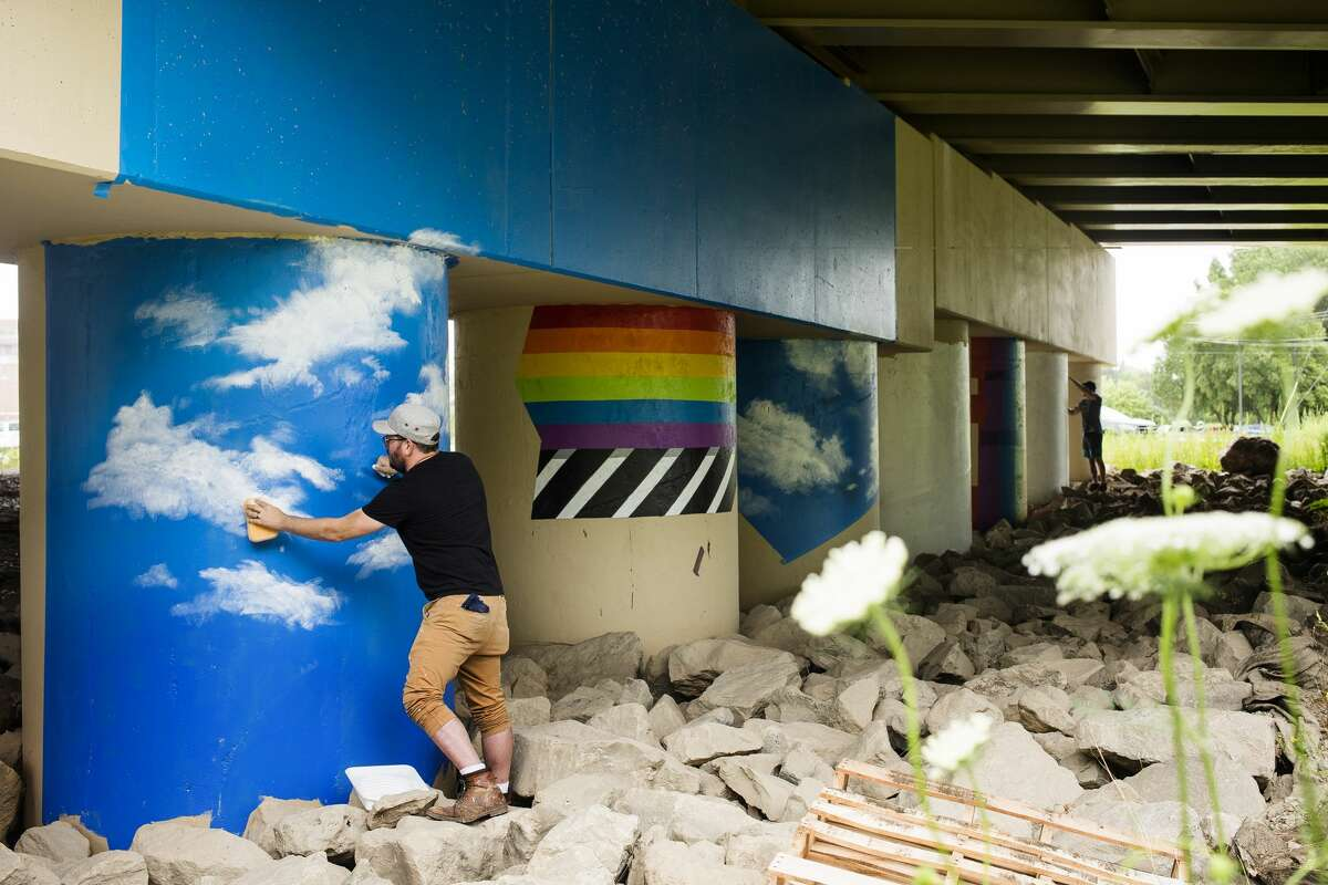 Cam DeCaussin, left, and Joey Salamon, right, work on the M-20 bridge mural project Wednesday, July 7, 2021 along the Pere Marquette Rail Trail in Midland. (Katy Kildee/kkildee@mdn.net)