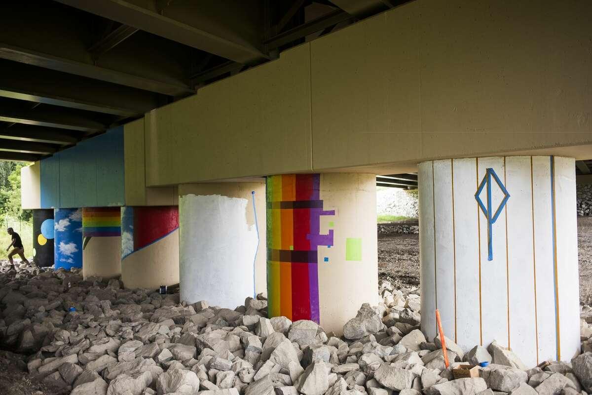 The M-20 bridge mural project is underway Wednesday, July 7, 2021 along the Pere Marquette Rail Trail in Midland. (Katy Kildee/kkildee@mdn.net)