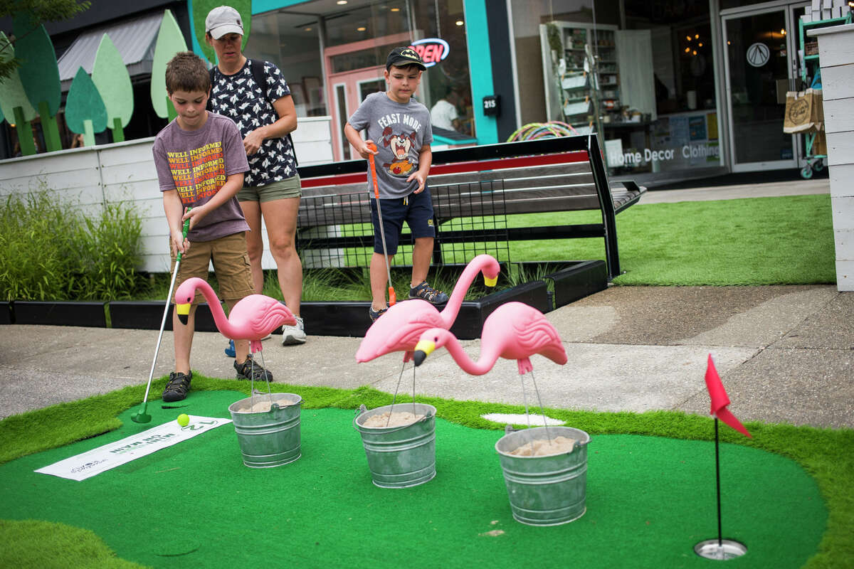 Nate VonFintel, 8, makes a putt while participating in Mini Golf on Main, hosted by the Midland Downtown Business Association, alongside his mom, Stephanie VonFintel, center, and younger brother Ted, 5, right, Wednesday, July 7, 2021 in downtown Midland. (Katy Kildee/kkildee@mdn.net)