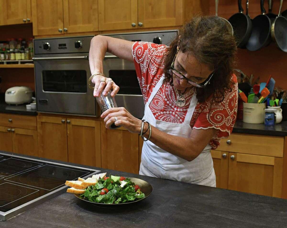 Caroline Barrett adds fresh ground pepper to her marinated chard salad with feta and herbs.(Lori Van Buren/Times Union)