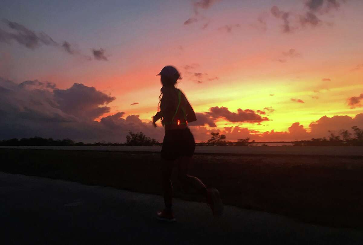 As the sun sets, Liza Howard runs on a bike path next to U.S. Route 1 during the May 15 Keys 100 ultramarathon from Key Largo to Key West in Florida. She began running before sunrise that morning in Key Largo and arrived in Key West after dark.