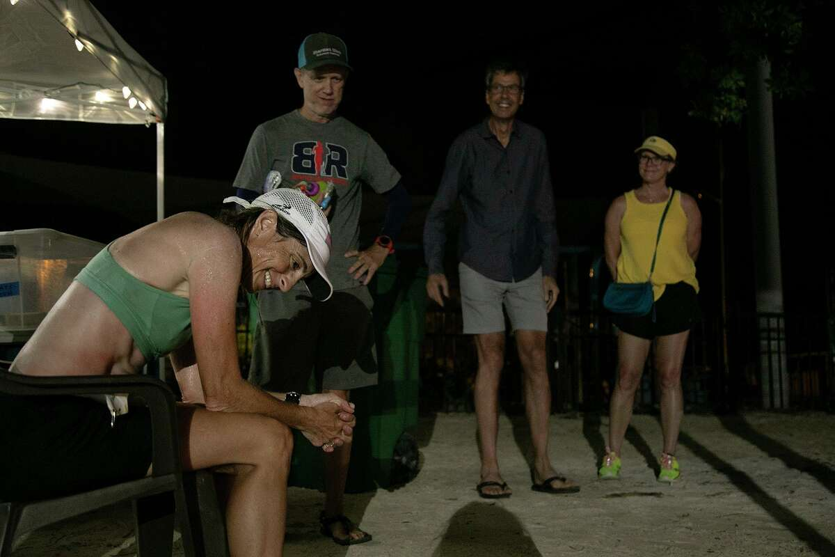 After running for 17 hours, 49 minutes and 24 seconds, Liza Howard rests after crossing the finish line of the Keys 100 in Key West near 11 p.m.