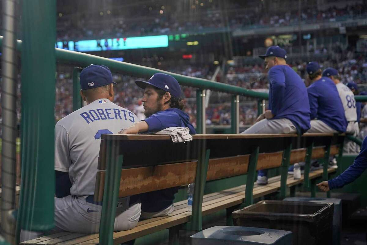 Los Angeles Dodgers manager Dave Roberts, left, talks with starting pitcher Trevor Bauer in the dugout during the fourth inning of a baseball game against the Washington Nationals, Thursday, July 1, 2021, in Washington. (AP Photo/Julio Cortez)