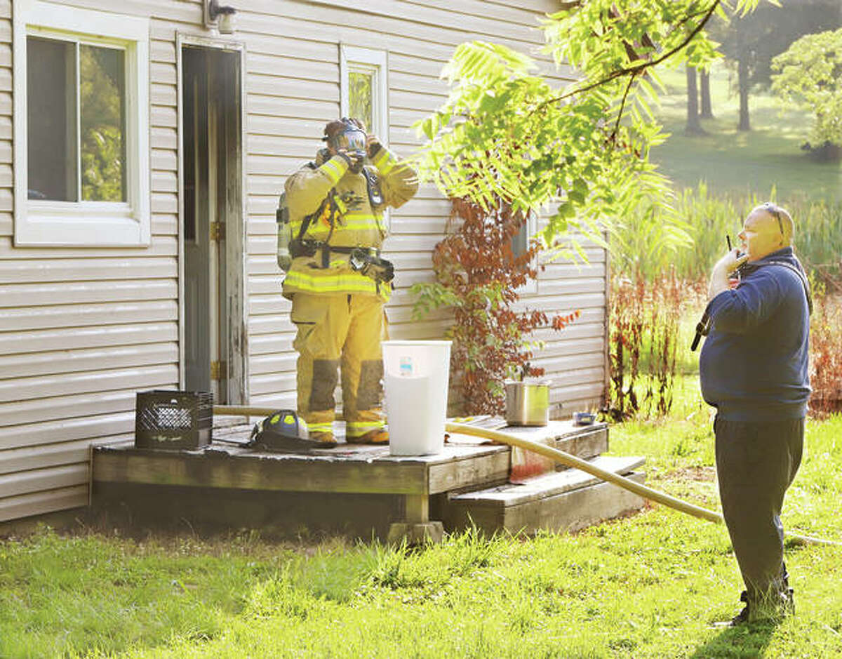 Rosewood Heights Fire Chief Tim Bunt, right, talks to responding firefighters Wednesday morning as a Cottage Hills firefighter prepares to enter an unoccupied house in the 600 block of Wood River Avenue in Cottage Hills. No injuries were reported.