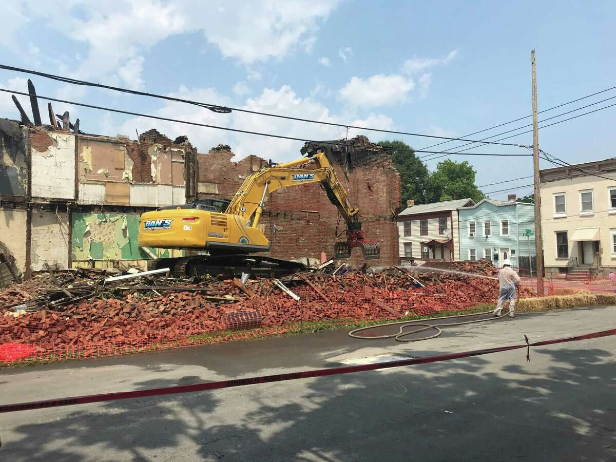 Equipment from Dan's Hauling and Demolition of East Greenbush is on the pile of bricks that remains after the fire-damaged building at 2401 Broadway in Watervliet, N.Y. was razed on Wednesday July 7, 2021. The buildings at 2403 and 2405 Broadway also will be torn down.