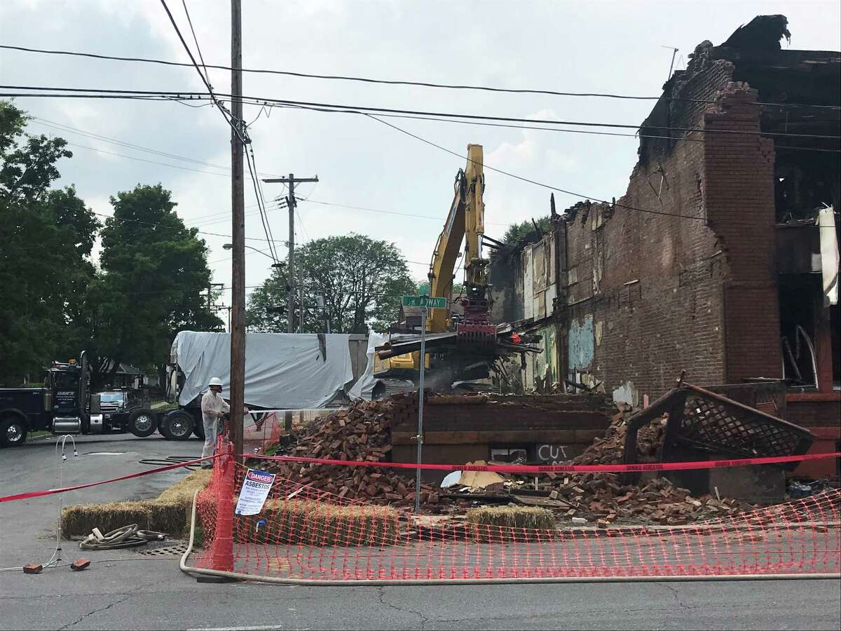 Workers from Dan's Hauling and Demolition of East Greenbush work on removing the debris that remains after the fire-damaged building at 2401 Broadway in Watervliet, N.Y. was demolished on Wednesday July 7, 2021. The buildings at 2403 and 2405 Broadway also will be torn down.