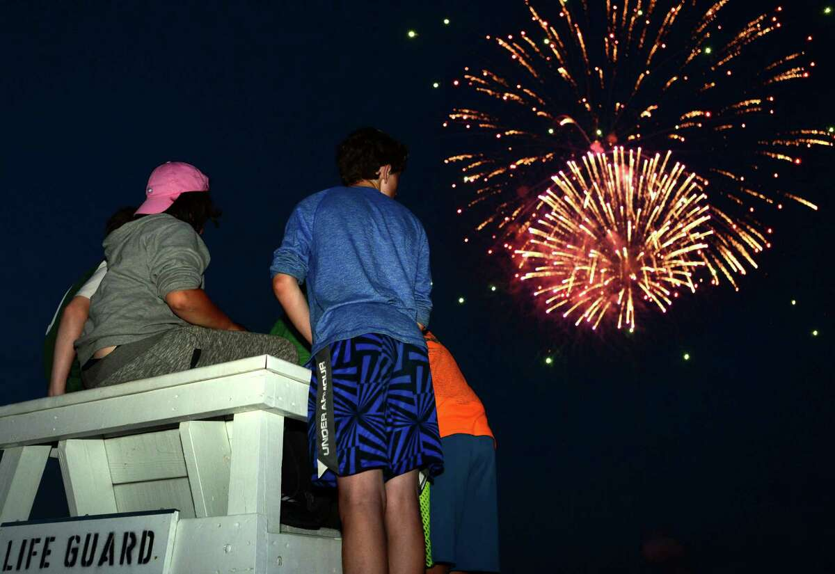 Locals gather for the annual fireworks show at Calf Pasture Beach on Wednesday, July 3, 2019, in Norwalk, Conn. The event was not held in 2020 and 2021 due to the coronavirus pandemic.