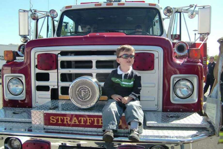 Not yet ready to drive, but ready to roll. A visitor enjoys a chance to get up close and personal to a fire truck during laset year's Junior Women's Club of Fairfield's Touch-a-Truck. This year's event runs 12 to 4 p.m., Sunday. Photo: Contributed Photo / Stamford Advocate Contributed