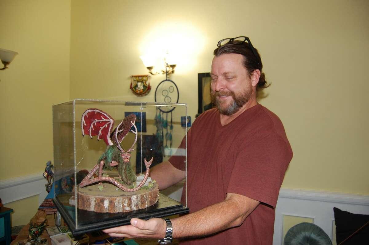 Dave Nunnally displays an intricate Piasa bird crafted by artist Nick Williams at It's Raining Zen.