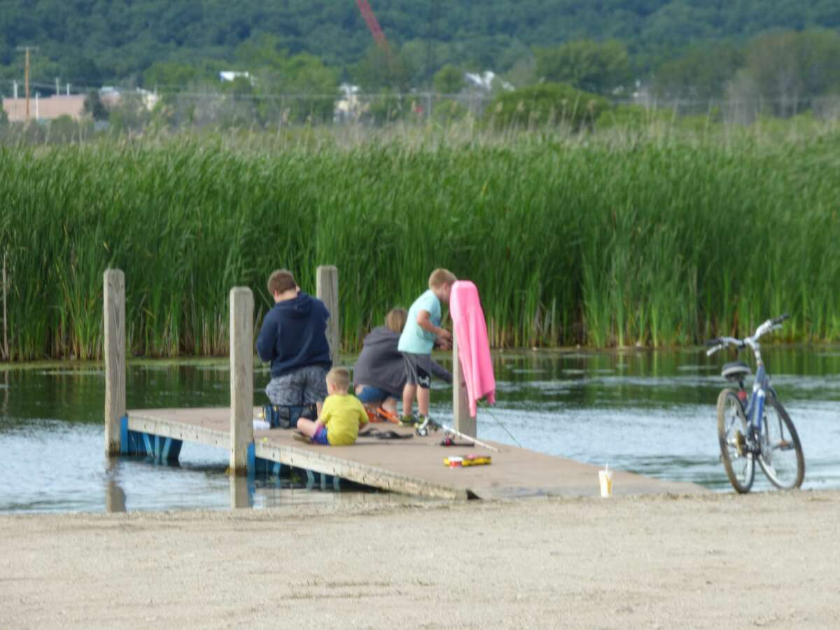A group of young anglers try their luck fishing off a dock last Friday at Penny Park.