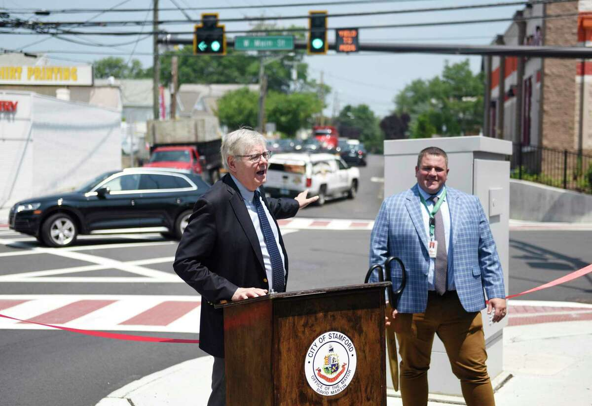 Stamford Mayor David Martin, left, and Stamford Transportation, Traffic & Parking Interim Bureau Chief Frank Petise speak at the ribbon-cutting for the new and improved intersection of West Avenue and West Main Street in Stamford on Wednesday.