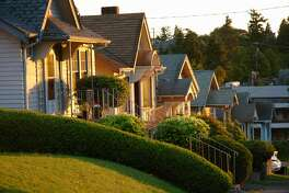 Early morning sun highlights the front of a hillside of houses in Seattle, Washington.