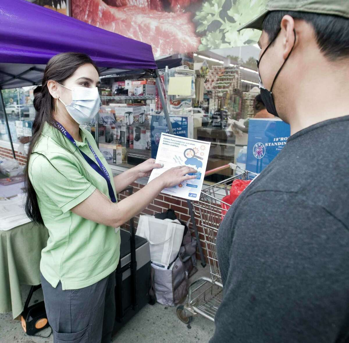 Jackie Felix, a nurse with the Ridgefield Visiting Nurse Association, explains COVID-19 vaccine information to Oscar Flores of Pawling, at CTown Supermarket in Danbury. Tuesday, June 22, 2021