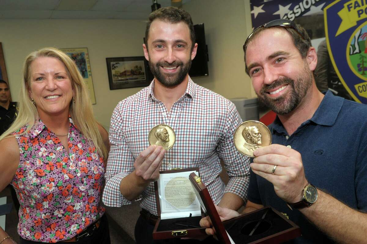 First Selectwoman Brenda Kupchick poses with brothers Jonathan Goldfarb, of Fairfield, and Matthew Goldfarb, of Howell, N.J. after they were presented with Carnegie Medals in Fairfield, Conn. July 7, 2021. The brothers received the medals Wednesday for their efforts to help save the life of a man and his dog who had fallen through the ice at Lake Mohegan in December 2019.