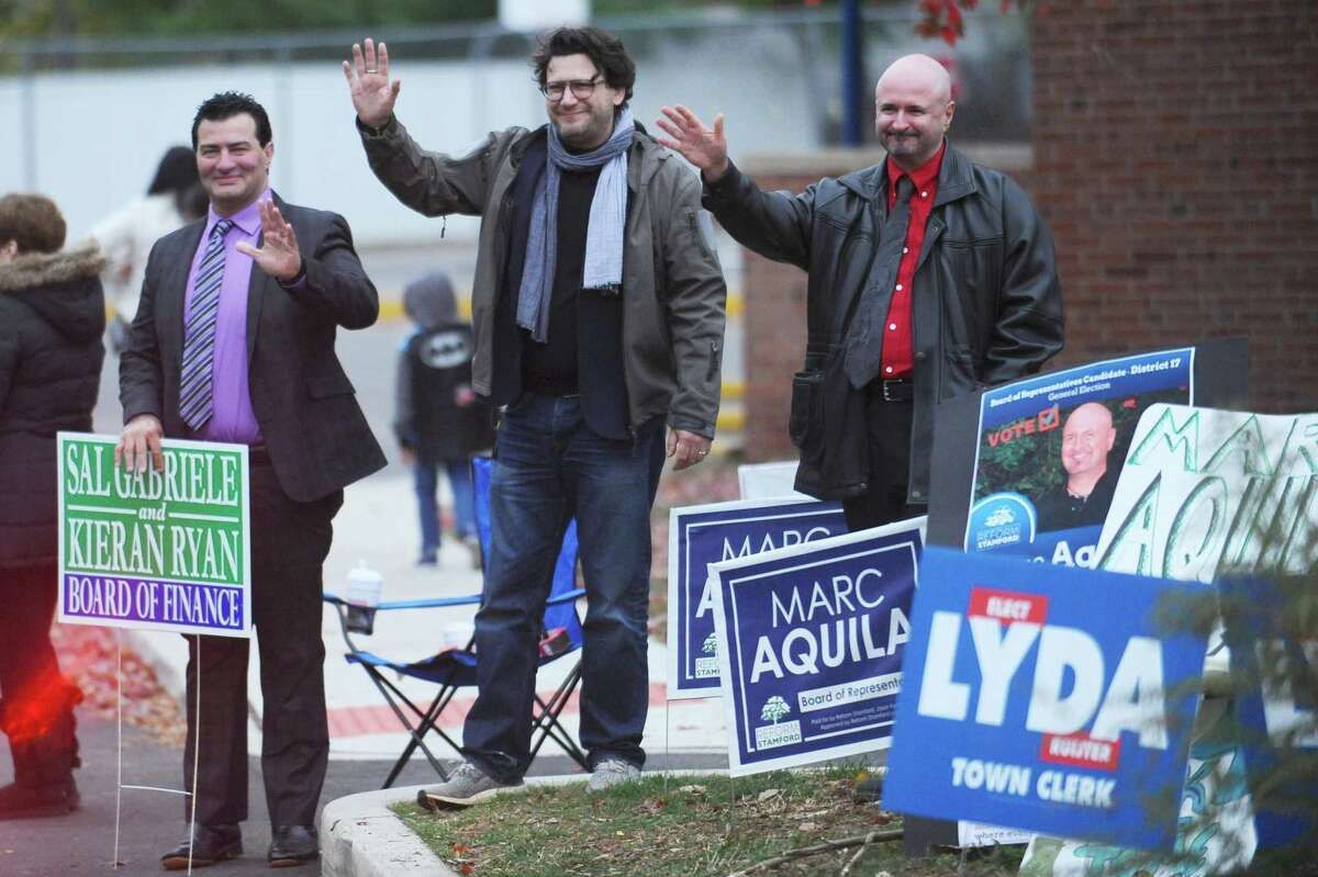 From left, Sal Gabriele, Marc Aquila and David Michel wave to voters as they enter the parking lot of Springdale School in Stamford in 2017.